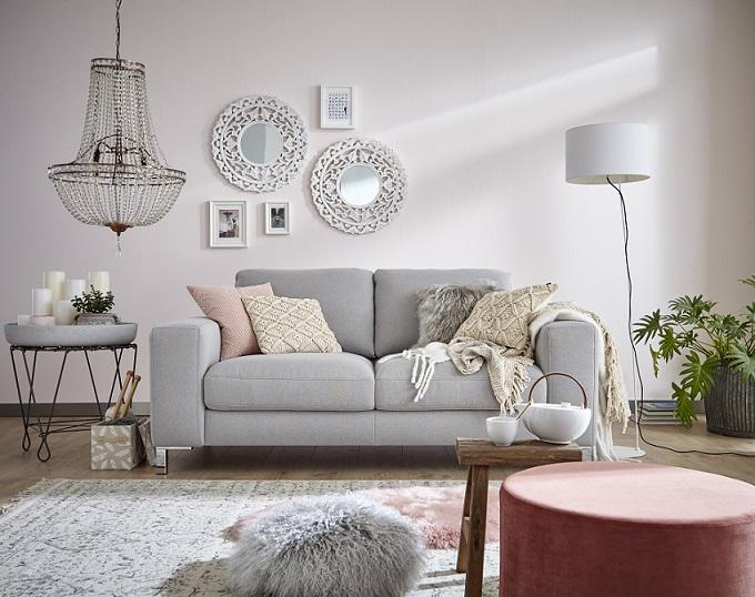Hellgraues Sofa mit vielen Deko-Kissen neben einem modernen Beistelltisch