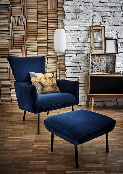 Blauer Sessel mit buntem Deko-Kissen und dem passenden Hocker vor einer Stehleuchte