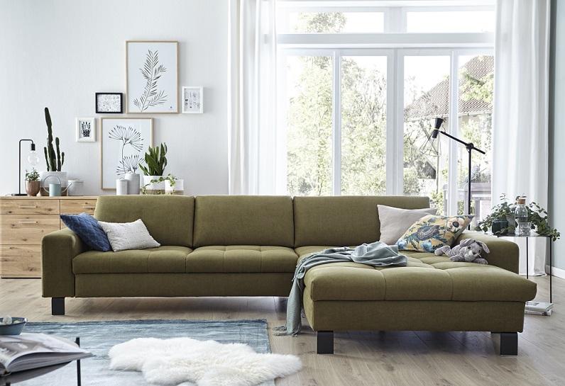Dunkelgrünes Sofa vor einer weißen Wand mit Wanddeko