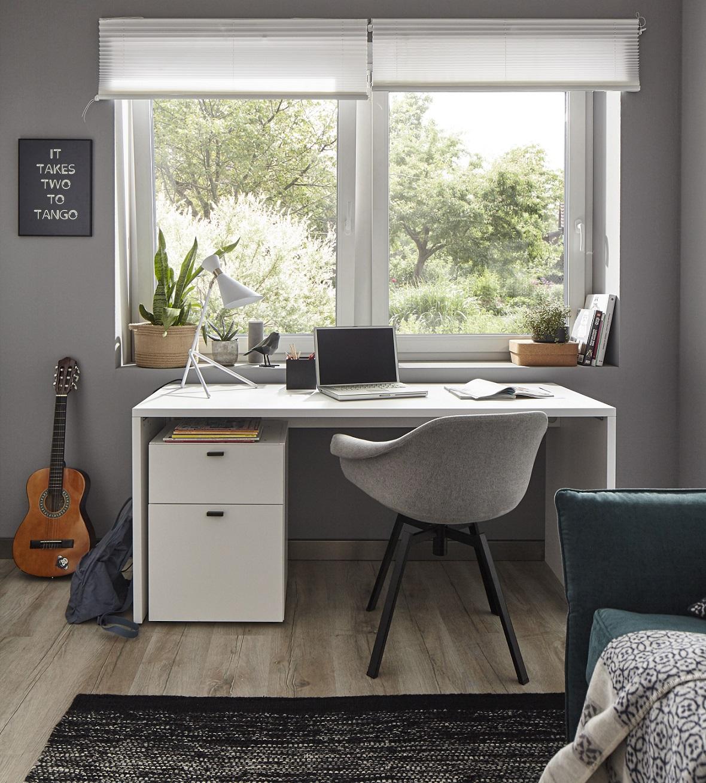 Weißer Schreibtisch mit moderner Lampe und einem hellgrauen Stuhl vor einem Fenster