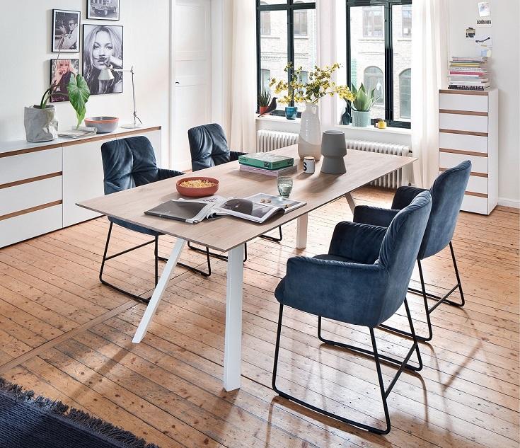 Esstisch im Skandi-Look umgeben von blauen Esszimmerstühlen