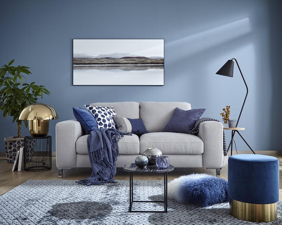 Graues Sofa mit blauen Deko-Kissen hinter einem modernen Beistelltisch