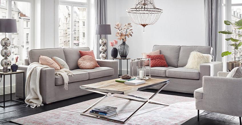 Graues Sofa mit rosa Kissen und rosa Blumen als Deko unter einem auffälligen Kronleuchter