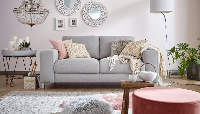 Hellgraues Sofa mit leicht rosafarbenen Kissen vor einer rosa gestrichenen Wand