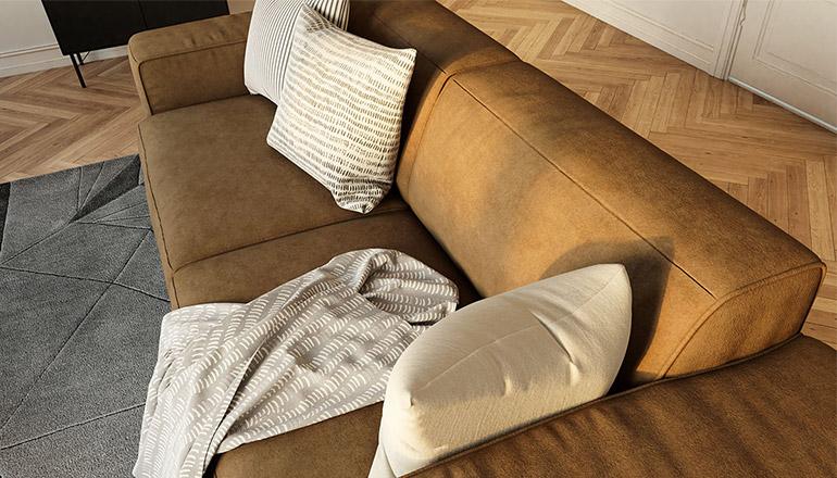 Nahaufnahme des olivgrünen Sofas mit weißen und beigefarbenen Kissen und einer Decke