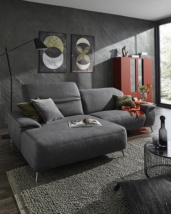 Dunkelgraues Zweisitzer-Sofa mit rotem Highboard vor anthrazitfarbener Wand