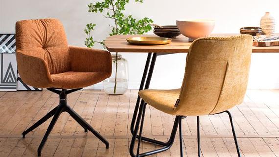 Orange- und gelbfarbener Stuhl um einen hölzernen Esstisch