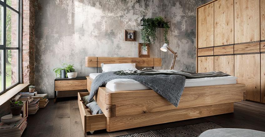 Bettgestell und Kleiderschrank aus massivem Holz vor einem hellen Fenster
