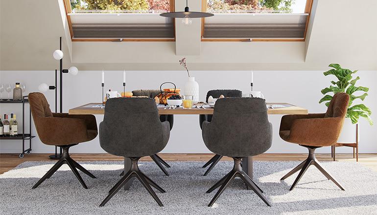 Esszimmer mit Dachschrägen und einem großen Esstisch sowie sechs gemütlichen Armlehnstühlen