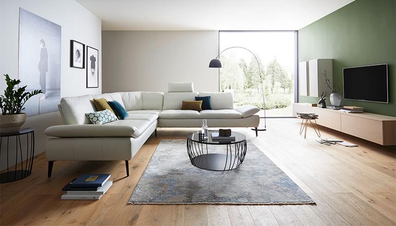 Weißes elegantes Ecksofa im modern eingerichteten Wohnzimmer mit schwarzem Couchtisch