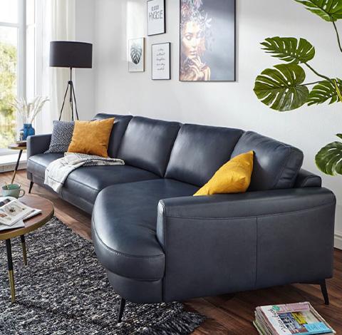 Dunkelblaues Sofa mit Deko, Kissen und Pflanzen