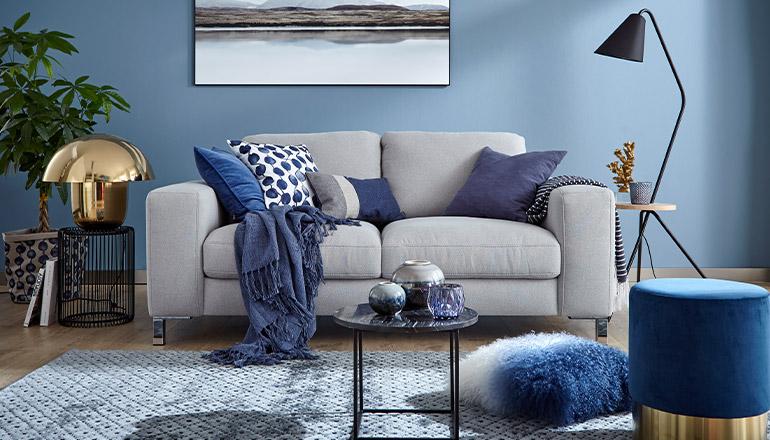 Graues Sofa mit blauen Deko-Kissen und einem Beistelltisch vor einer blauen Wand