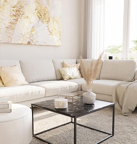 Sofa in Cremeweiß vor einem schwarzen Couchtisch mit Marmor-Optik