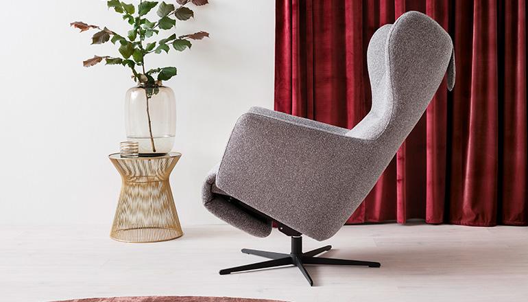 Grauer Relaxsessel mit einem modernen Beistelltisch vor einem roten Vorhang