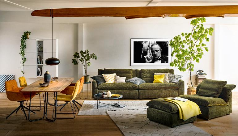 Wohnbereich mit Esstisch und Stühlen und einem Sofa sowie einem Sessel mit Hocker