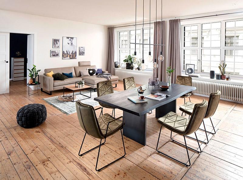 Schwarzer Massivholztisch umrandet von olivgrünen Stühlen vor beiger Couch