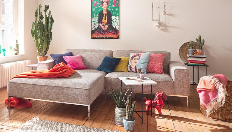 Graues Sofa mit Dekokissen und zwei bunten Wohndecken