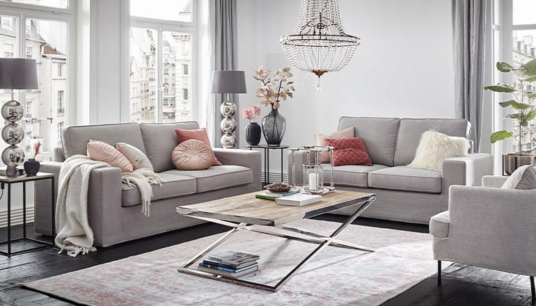 Graue Sofa Garnitur unter glänzendem Kronleuchter und luxuriösen Tischleuchten