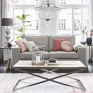 Graue Zweisitzer Couch mit rosa Kissen unter einem eleganten Kronleuchter