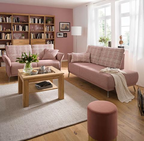 Wohnzimmer mit zwei rosa Sofas und einem rosa Hocker vor einer rosa Wand