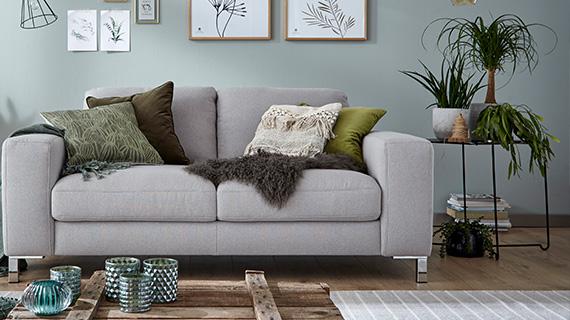 Zierlicher, schwarzer Beistelltisch mit Pflanzen neben einem grauen Sofa