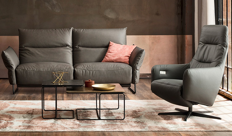 Grauer Relaxsessel neben einem grauen Sofa und einem Couchtisch