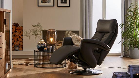Schwarzer Sessel mit Relaxfunktion neben einem modernen, dekorierten Couchtisch