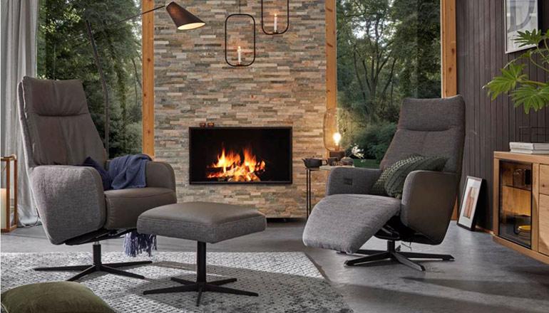 Ein grauer Sessel mit Relaxfunktion und einer mit dem passenden Hocker vor einem Kamin