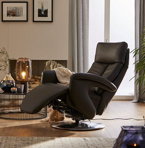 Drehsessel aus schwarzem Leder und mit Relaxfunktion neben einem Beistelltisch