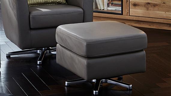 Viereckiger grauer Hocker aus Leder passend zu dem Sessel mit Relaxfunktion im Hintergrund