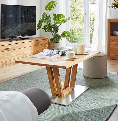 Hölzerner Couchtisch mit modernem Gestell vor einem Lowboard aus Massivholz