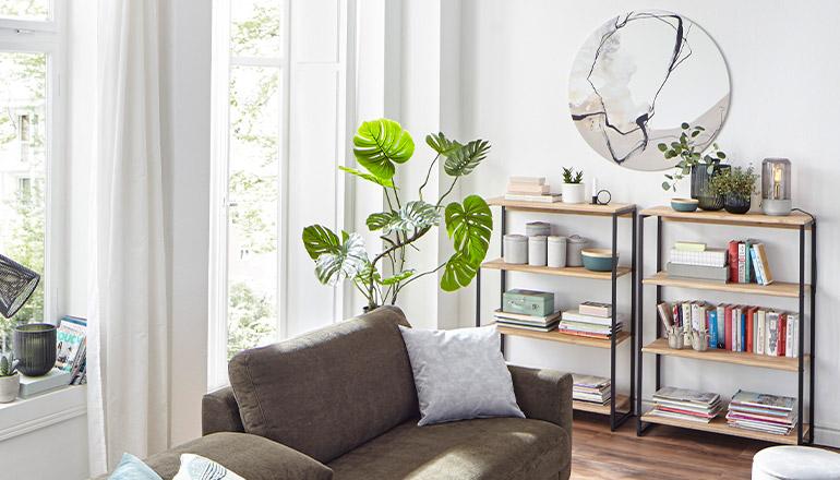 Zwei Regale mit hölzernen Einlegeböden dekoriert mit Büchern, Vasen und Lampen