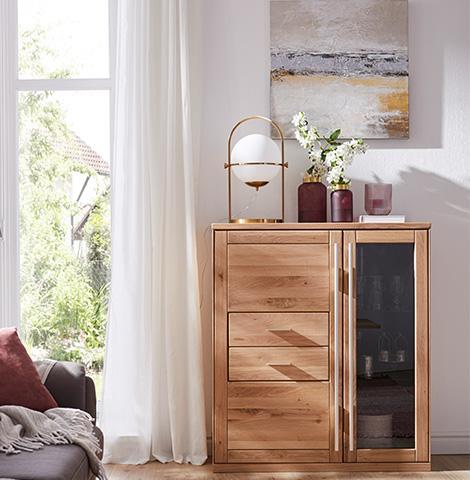 Hölzernes Highboard mit einer Glastür dekoriert mit Vasen und einer Lampe