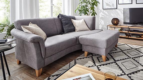 Zweisitzer-Sofa wird zum Ecksofa mit passendem Hocker davor in Hellgrau mit Holzfüßen