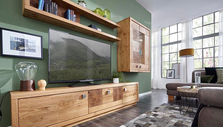 Wohnwand aus Massivholz mit Hirnholzapplikationen vor einer kräftig in Grün gestrichenen Wand