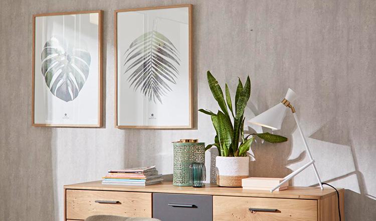Hölzerne Kommode geschmückt mit einer Lampe, einer Pflanze und Vasen