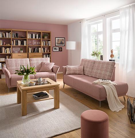 Zwei rosa Sofas sowie ein Hocker und ein hölzerner Couchtisch vor einem Bücherregal