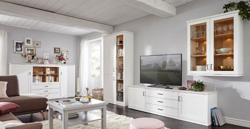 Weiß lackierte Wohnwand neben Highboard und einer braunen Couch