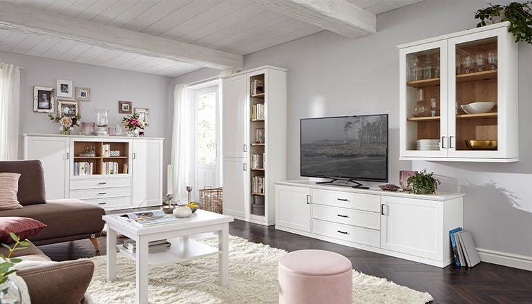 Wohnzimmer im Landhausstil mit weißen Möbeln wie Highboard, Lowboard und Couchtisch