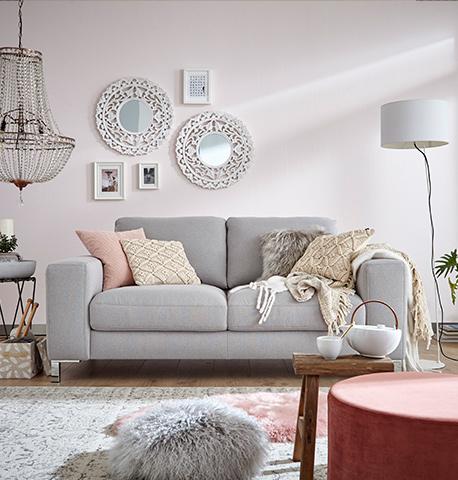 Graues 2-Sitzer Sofa mit diversen Deko-Kissen und einer Wohndecke vor dekorierter Wand