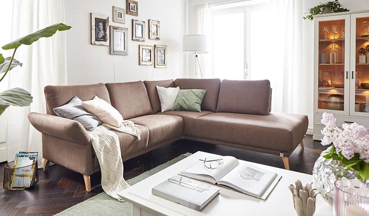 Braunes Ecksofa mit bunten Kissen in einem Wohnzimmer im Landhaus-Stil