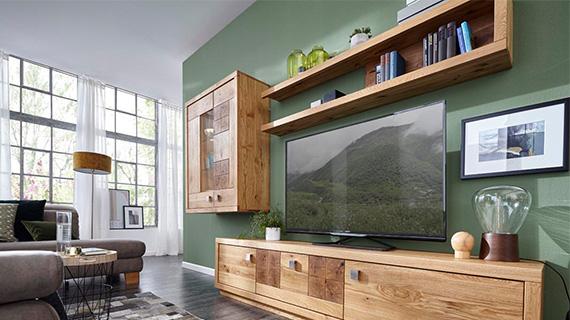 Wohnwand aus hellbraunem Massivholz vor einer waldgrünen Wand