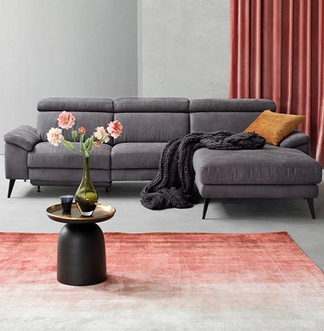 Graues Dreisitzer-Sofa in Wildlederoptik vor elegantem Couchtisch in Gold und Schwarz