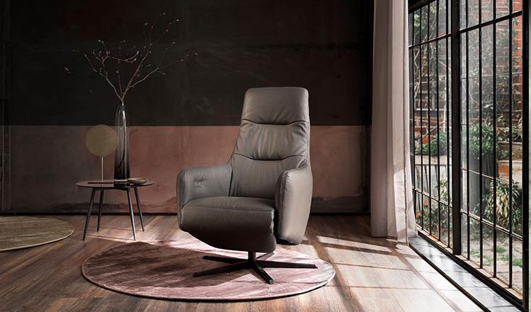 Ovaler Beistelltisch dekoriert mit einer extravaganten Vase neben einem grauen Sessel
