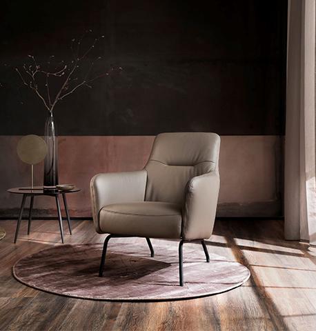 Sitzgruppe aus dunkelgrauem Leder um dezent eingerichteten Wohnzimmer
