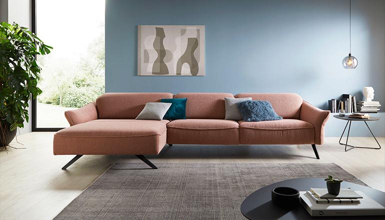 Pastellfarbenes Sofa im Pfirsich-Ton vor hellblauer Wand