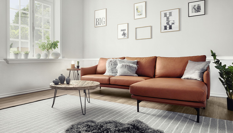 Cognacfarbenes Sofa im weiß-grau eingerichteten Wohnzimmer vorSchafffell