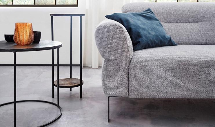 Graues Sofa mit Stoffbezug und blauem Deko-Kissen neben zwei runden Beistelltischen