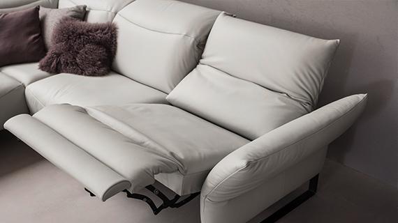 Weißes 3-Sitzer Sofa aus Leder mit einer Relaxfunktion und dunklen Deko-Kissen