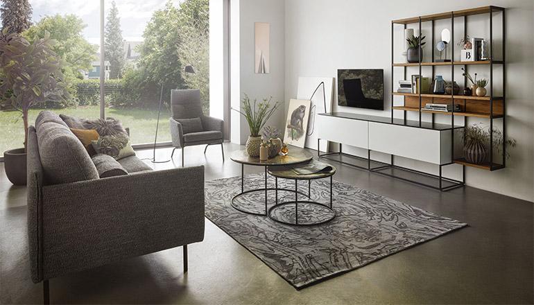 Grauer Zweisitzer vor einer reduzierten Wohnwand aus Holz und Lack